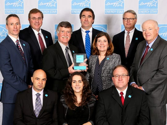 Corning Inc. employees recently accepted a prestigious award. Front row from left: Luiz Ferri, Kelly Stemcosky and Gene Gano. Middle row: J.T. Hufnagel, Bruce Hostrander, Beth Vine and Patrick Jackson. Back row: Michael Donnelly, John Palladino and Howard Stanley.
