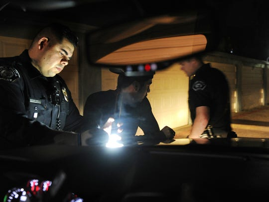 Chris Rivera (left), a second-year Santa Paula Police Department officer, writes a citation after making a traffic stop,