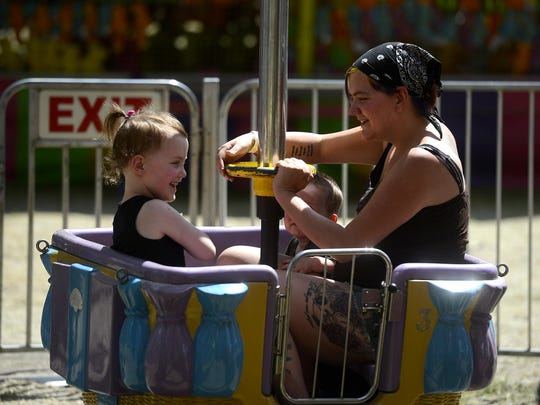 Kendra Wilson rides a kid carnival ride with her kids Emilie, age 5, and Taiden, age 2, on Thursday afternoon at the Montana State Fair.