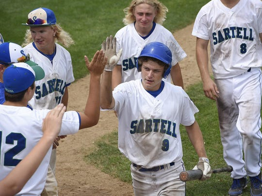 Sartell's Keenan Lund is congratulated by teammates after scoring a run in the ninth inning of a game against Sauk Rapids in St. Cloud.
