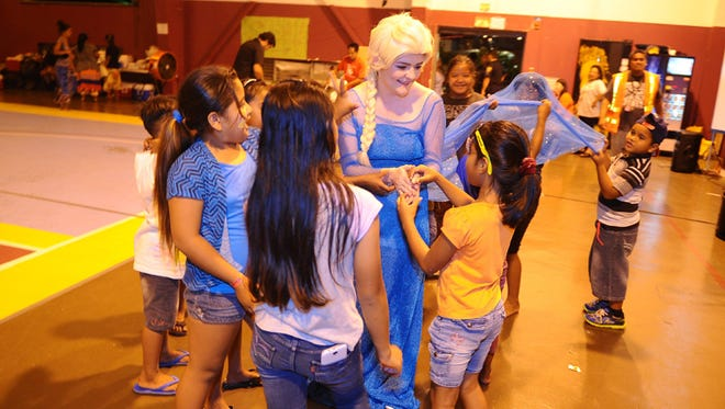 "From the Disney movie ""Frozen,"" character Queen Elsa, portrayed by Princess Parties Guam's Chloe Conrad, interacts with children at the Tamuning gym on May 22. The children are from families temporarily housed at the gym after being displaced from their homes after the passage of Typhoon Dolphin near Guam on May 15. Princess Parties Guam was at the shelter to entertain the kids and for a screening of the movie, ""Frozen."""