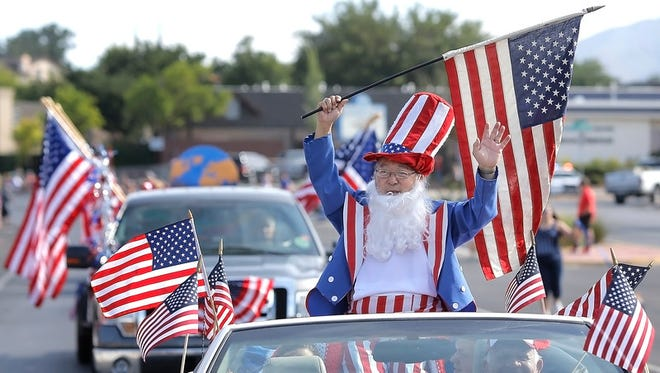 """Uncle Sam waves at spectators during the Rotary Club of West El Paso Fourth of July Parade in 2015 as it made its way down Shadow Mountain. """
