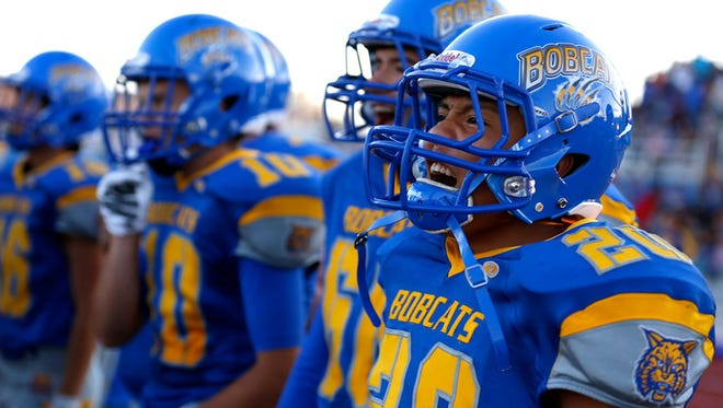 Bloomfield's Jonathan Begaii, right, cheers on his team from the sidelines during a Sept. 11 game against Socorro at Bobcat Stadium in Bloomfield.