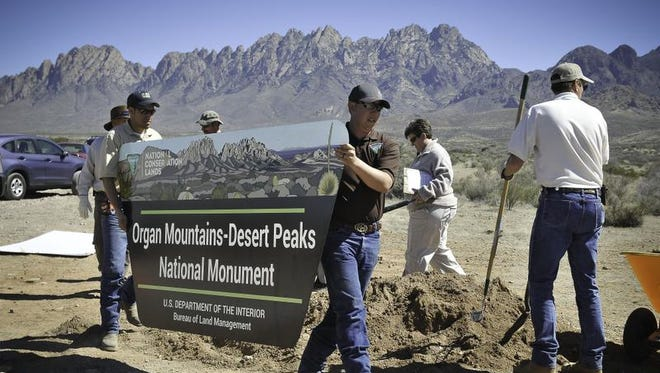 Workers install a sign at the new Organ Mountain-Desert Peaks National Monument in Las Cruces. Almost a half-million acres in southern New Mexico were designated as a national monument two years ago, and now members of the state's congressional delegation are pushing for portions of the OMDP area to be set aside as wilderness.