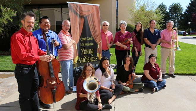 Members of a group that offer exposure to orchestral music, dance, visual art and poetry to local students gather in front of the Farmington Civic Center on Friday.