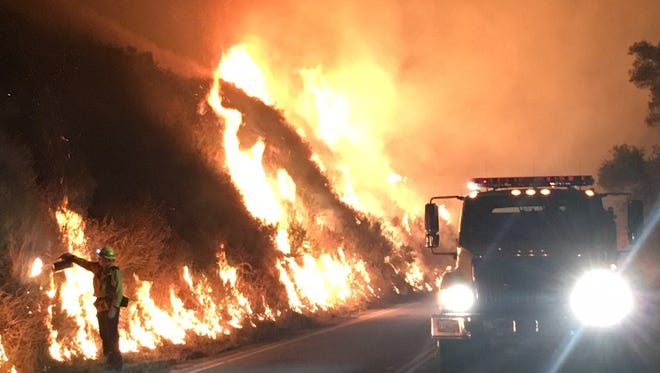 A Ventura County firefighter uses fire to fight fire on Thursday night at the Alamo Fire in San Luis Obispo County.