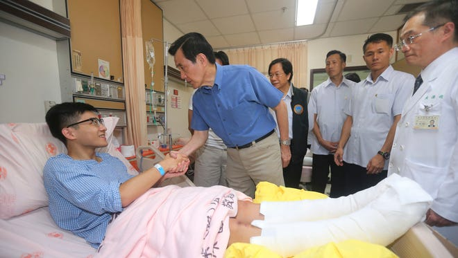 Taiwanese President Ma Ying-jeou shakes hands with a victim injured in an accidental explosion during a music concert, in New Taipei City, Taiwan, Sunday, June 28, 2015.