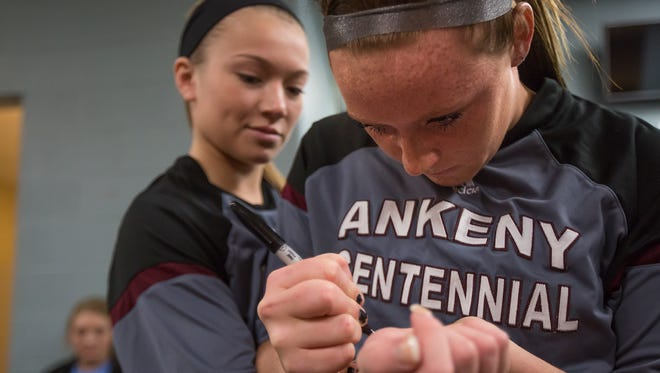 Ankeny Centennial basketball player Emily Fontana, right, writes on teammate Sydney Wycoff wrist before playing in the state tournament at Wells Fargo Arena in Des Moines, Iowa, on Wednesday, March 2, 2016. They both lost their parents to brain cancer in the past year. In their memory, they write the initials of their late parents, Amy Staggs-Fontana and Greg Wycoff, on their wrists before each game.