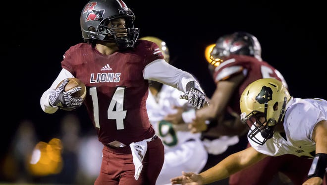 Mesa Red Mountain's Lance Lawson (14) runs with the ball in the first half of the high school football game between Basha and Red Mountain at Red Mountain High School on Friday, September 9, 2016 in Mesa.