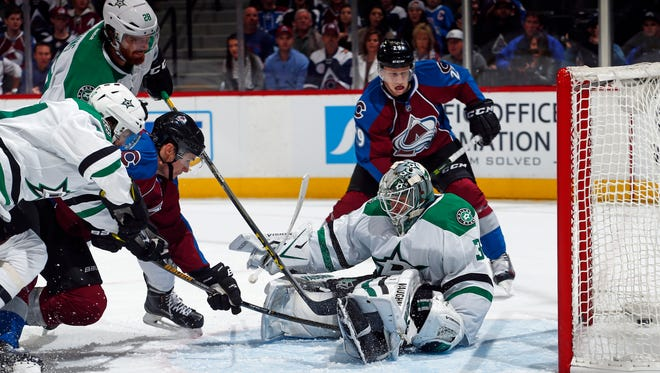 Dallas Stars' Johnny Oduya (47) and Stephen Johns (28) defend as Colorado Avalanche center Joe Colborne (8) scores a goal against Stars goalie Antti Niemi (31), while Avalanche's Nathan MacKinnon (29) watches. (AP Photo/Jack Dempsey)