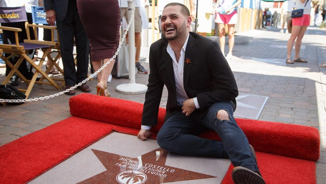 Designer Michael Costello poses for photographers with his star on the Palm Springs Walk of Stars, Monday, March 20, 2017.