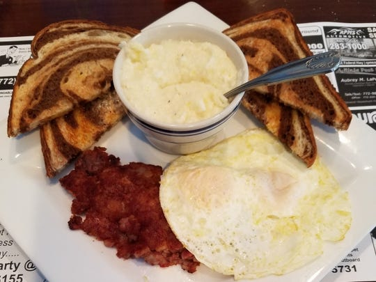 A Sailfish Cafe breakfast platter is two eggs over medium, grilled corned beef hash, accompanied by home fries and marbled rye toast.