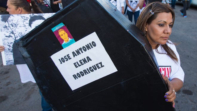 Araceli Rodríguez carries a makeshift coffin for her son during a march in Nogales, Sonora, Mexico Friday October 10, 2014. It's been two years since 16-year-old José Antonio Elena Rodríguez was shot by a Border Patrol agent who fired through the fence in Nogales.