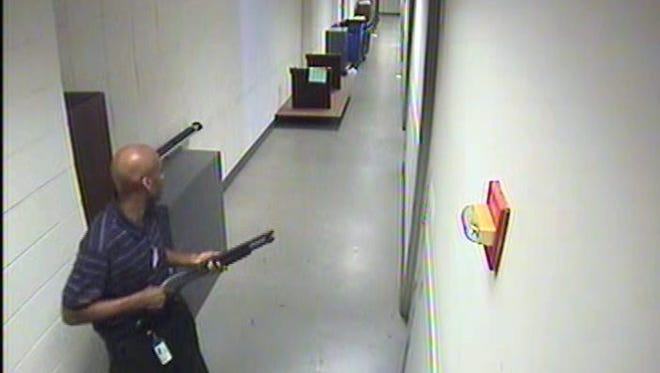 A surveillance image released by the FBI shows Aaron Alexis in the hallway of building #197 carrying a Remington shotgun.