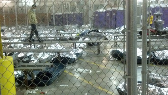 Hundreds of unaccompanied immigrant children sleep under foil blankets at a holding center in Nogales, Ariz., on Friday after being shipped to Arizona from Texas.