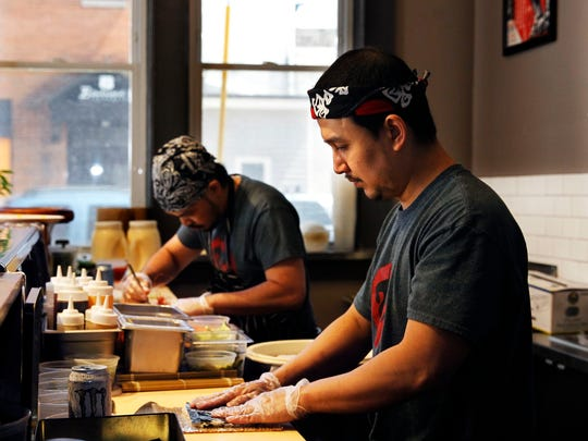 Chef-owner Thitichai (Jif) Rukchon (right) and Tom Boontos prepare sushi in the dining room at Hungry Sumo.