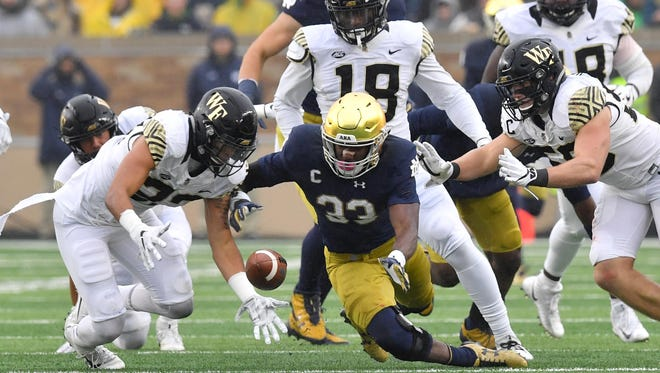 Nov 4, 2017; South Bend, IN, USA; Wake Forest Demon Deacons linebacker Justin Strnad (23) and Notre Dame Fighting Irish running back Josh Adams (33) dive for a loose ball in the second quarter at Notre Dame Stadium. Mandatory Credit: Matt Cashore-USA TODAY Sports