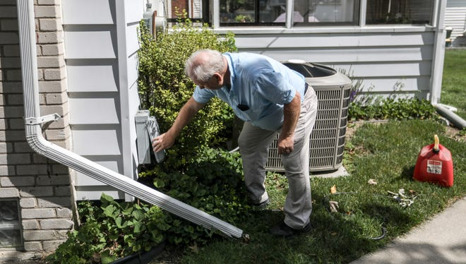 Charles Semchena. Jr., 65, of Royal Oak shows where he hooks up the gas-powered generator at his 95-year-old mother's home in Royal Oak on Thursday, June 21, 2018.