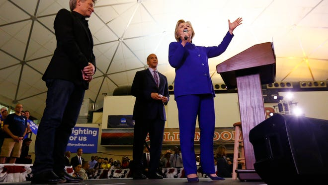 Hillary Clinton stands on stage with musician Jon Bon Jovi and Sen. Cory Booker, D-N.J., while speaking during a campaign stop at the Newark campus of Rutgers University.