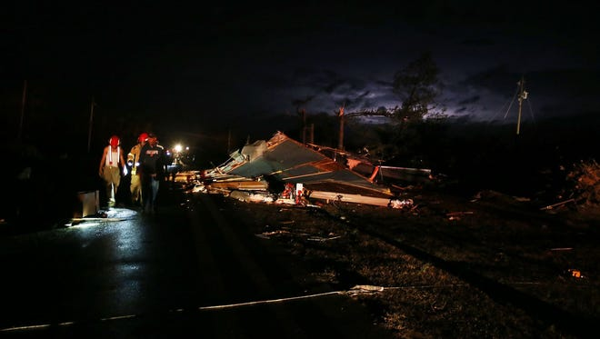 People look at debris after a storm passed through the Sapps mobile home park destroying many homes in Sapps, Ala., just outside of Aliceville on Tuesday, Feb. 2, 2016. Authorities say a large tornado in rural western Alabama left a trail of damage as powerful storms moved into the state.