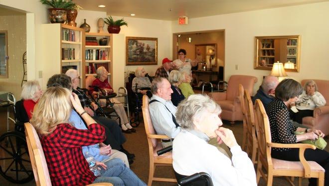 Residents and community members listen to Joel Henderson's presentation of the State of Oregon's program Talking Books at Woodland Residential Inn on February 25.