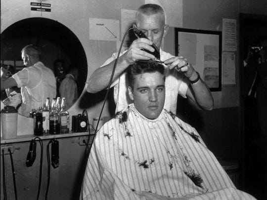 Elvis Presley gets his first Army haircut at Fort Chaffee, Ark., from James B. Peterson.
