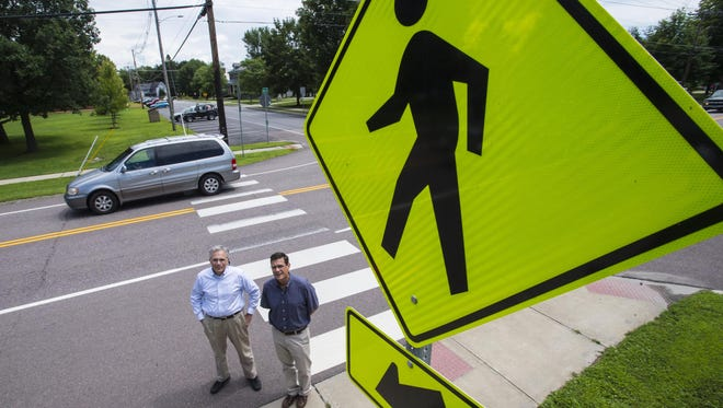 Steven Antinozzi (left) and Mark Gamble, co-chairs of the bike and pedestrian paths committee in Shelburne, are seen at a crosswalk on Route 7 in Shelburne on Wednesday, July 22, 2015. The town plans to expand the sidewalk from in front of the town offices to the covered bridge in front of the Shelburne Museum.  Currently people have to cross the busy road and cross back over again to get to the museum.