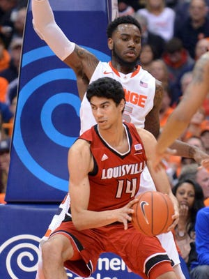 Feb 18, 2015; Syracuse, NY, USA; Louisville Cardinals forward Anas Mahmoud (14) looks to get the ball past Syracuse Orange forward Rakeem Christmas (25) during the second half of a game at the Carrier Dome. Syracuse won the game 69-59. Mandatory Credit: Mark Konezny-USA TODAY Sports