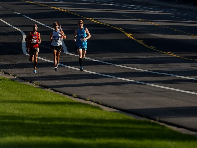 The lead runners in the Colorado Run half-marathon head down South Overland Trail Monday, September 1, 2014. Michael Chavez, right, won the race with a time of 1:11:36. Paul Petersen, center, finished one second behind for second place.