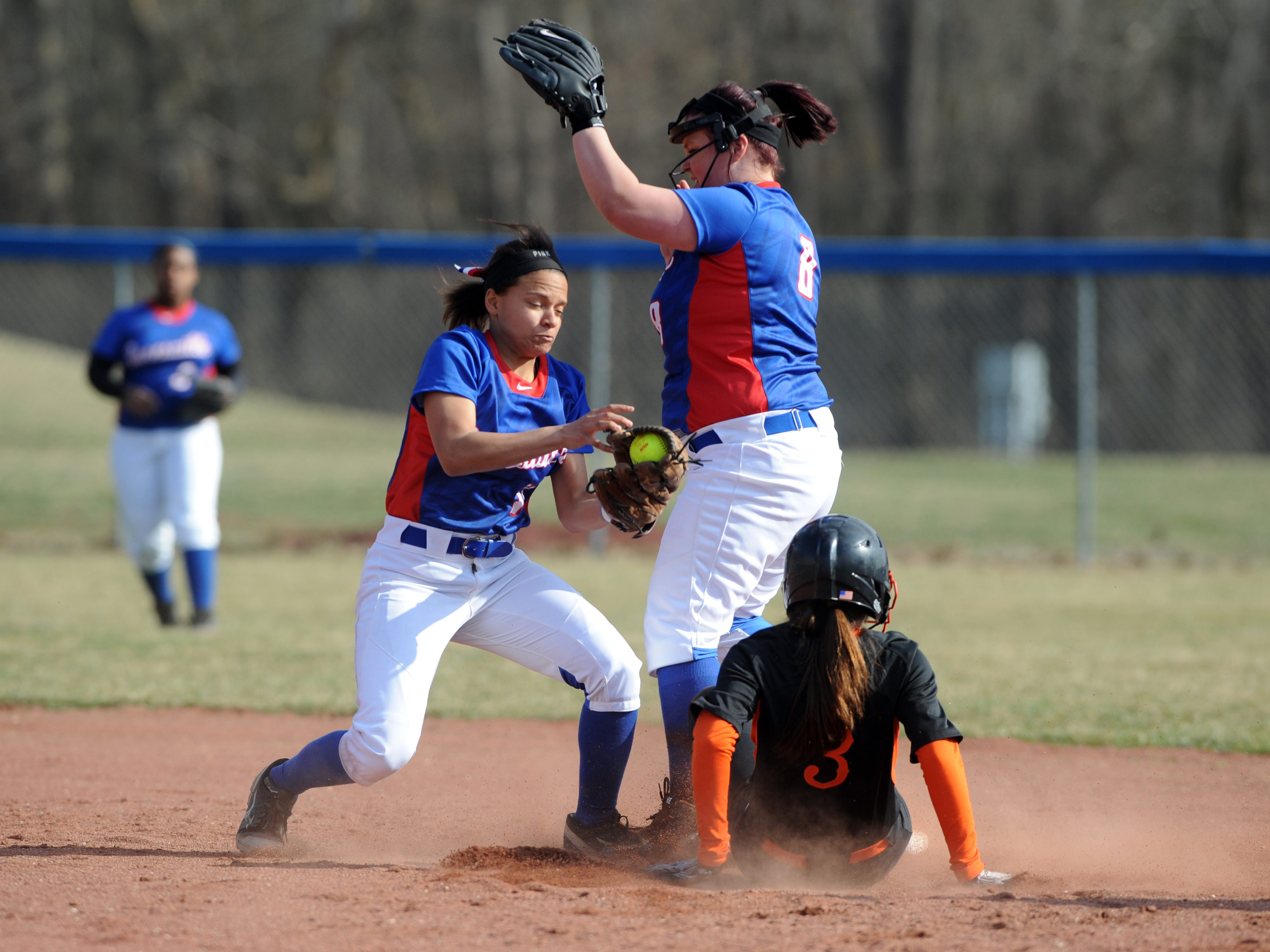 Marietta's Kendall Hartline safely slides into second base past Zanesville's Morgan Smith (12) during the first inning of a game at Zanesville High School.