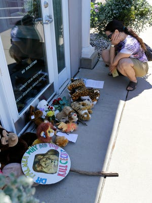 Activist Lisa Berger, of St. Paul, Minn., reads a note among notes and stuffed animals outside Dr. Walter James Palmer's dental office in Bloomington, Minn., on July 29, 2015.