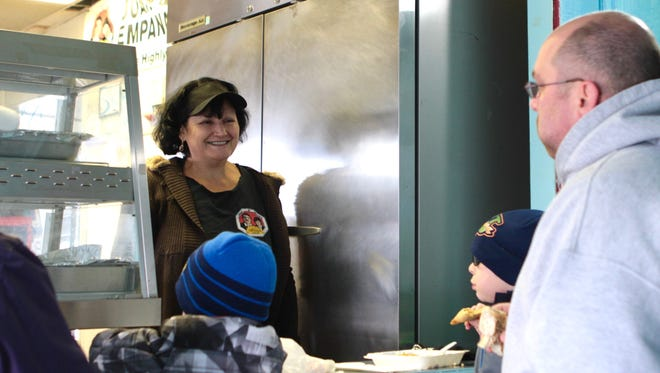 Co-owner Maria Contreras speaks with customers at Juan and Maria's Empanada Stop Saturday.