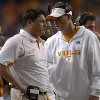 Tennessee head coach Lane Kiffin talks with assistant coach Ed Orgeron during the Chick-Fil-A Bowl Thursday, Dec. 31, 2009 in Atlanta.