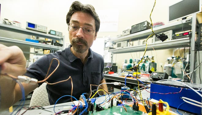 Jeffery Pilgrim, owner of Vista Photonics, works in his home optics lab on Tuesday, March 8, 2016. Pilgrim does research for NASA and recently received an EPA grant for further work on pollution.