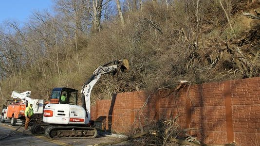 Workers remove trees after a landslide closed part of Loveland-Madeira Road in Indian Hill near Interstate 275.