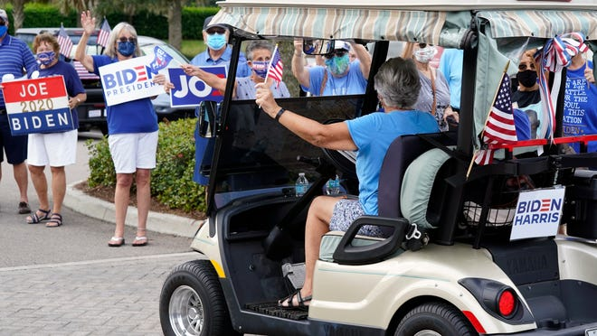 Supporters cheer and wave signs as voters arrive at the Sumter County Elections office to cast their ballots after taking part in a parade of over 300 golf carts supporting Democratic presidential candidate Joe Biden during early voting Wednesday in The Villages, Fla.