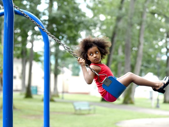 Faith Tyson swings at Rec Park in Binghamton on June