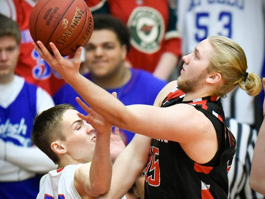 Rocori's Austin Overman (right) gets a shot off over Apollo's Ben Giese during the first half Saturday at Halenbeck Hall.