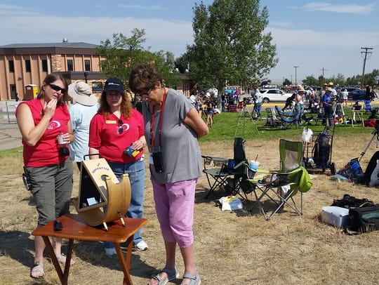 """Tourists gather around the """"Sunspotter"""" eclipse viewing"""