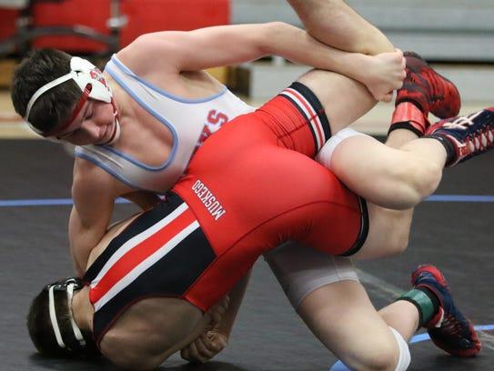 Arrowhead's Keegan O'Toole brings Muskego's Tyler Schanen into the mat in a 132-pound match during a dual meet at Arrowhead in December.