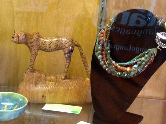 A sleek cheetah in wood and richly colored necklace are displayed in Ruidoso.