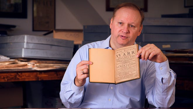 "In this November 2013 photo provided by Bonhams, Eric Caren displays an item from his document collection, ""A Brief History of the Warr With the Indians in New England,"" at the Caren Archive in Lincolndale, N.Y.  Caren, who has amassed what is considered one of the largest private collections of historical papers in the United States, will auction nearly 300 items from  his collection in April at the Manhattan location of Bonhams. The items for sale range from Revolutionary War documents describing the battles of Lexington and Concord to a mug shot of Western outlaw Butch Cassidy. (AP Photo/Bonhams)"