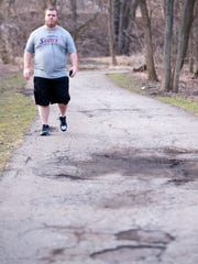 Jason Schrad of Lansing walks Tuesday along the Red Cedar River on the Lansing River Trail. Schrad said many spots on the trail need to be repaved. This particular section of the trail, from the railroad west of Interstate 496 to the connector to Fidelity Road has an estimated construction cost of $69,050.