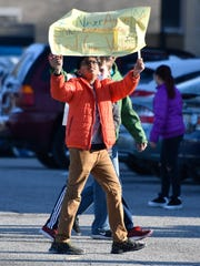 A student holds up a sign protesting gun violence at
