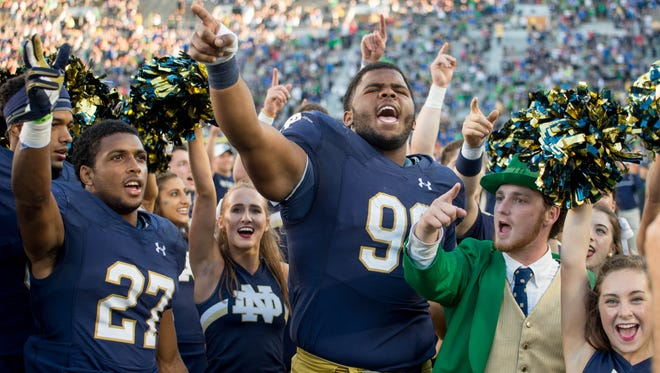 Sep 10, 2016; South Bend, IN, USA; Notre Dame Fighting Irish cornerback Julian Love (27) defensive lineman Jerry Tillery (99) and the Notre Dame leprechaun celebrate after Notre Dame defeated the Nevada Wolf Pack 39-10 at Notre Dame Stadium. Mandatory Credit: Matt Cashore-USA TODAY Sports