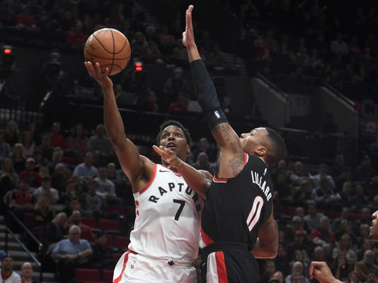 Toronto Raptors guard Kyle Lowry drives to the basket on Portland Trail Blazers guard Damian Lillard during the first quarter of an NBA basketball game in Portland, Ore., Monday, Oct. 30, 2017. (AP Photo/Steve Dykes)