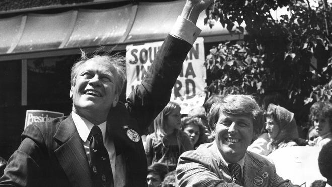 Gerald Ford waves during the presidential motorcade down Main Street, which also featured Mayor Lloyd and Indiana Governor Otis Bowen, culminating in a rally held at the Vanderburgh Auditorium.