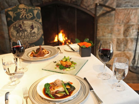 A table set for two by the fireplace in the Oak Room at Equus at the Castle on the Hudson in Tarrytown.