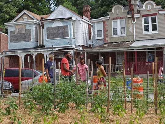 Members of the community gather for a few words about the new community garden on Wednesday in Wilmington. One aim of the garden project is to employ at-risk youth to care for the garden and set up a produce stand.