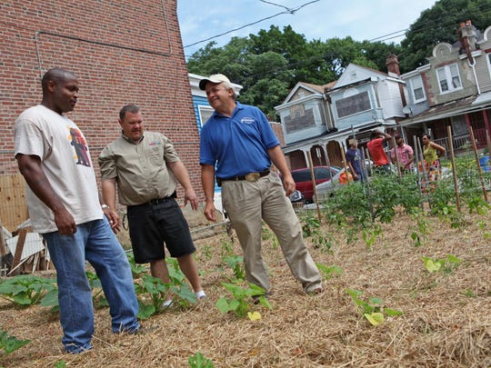 Matthew Williams, executive director of Conscious Connections Inc., gets a few irrigation tips from Mike Wasylkowski (center) and John Clendaniel with Delaware State University's Small Farm program at the new community garden on 22 E. 23rd St. Wednesday in Wilmington.